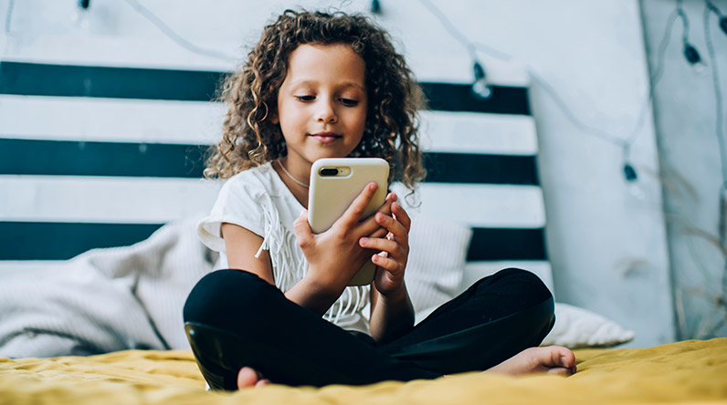 Little girl playing on a tablet Shutterstock