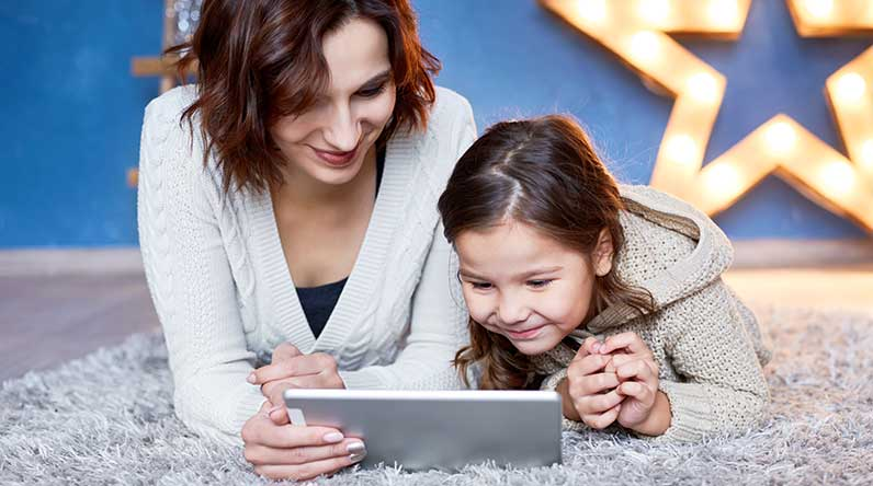 Mother and daughter looking at tablet / Shutterstock
