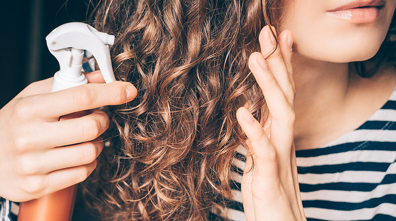 Woman spraying product on curly hair / Shutterstock