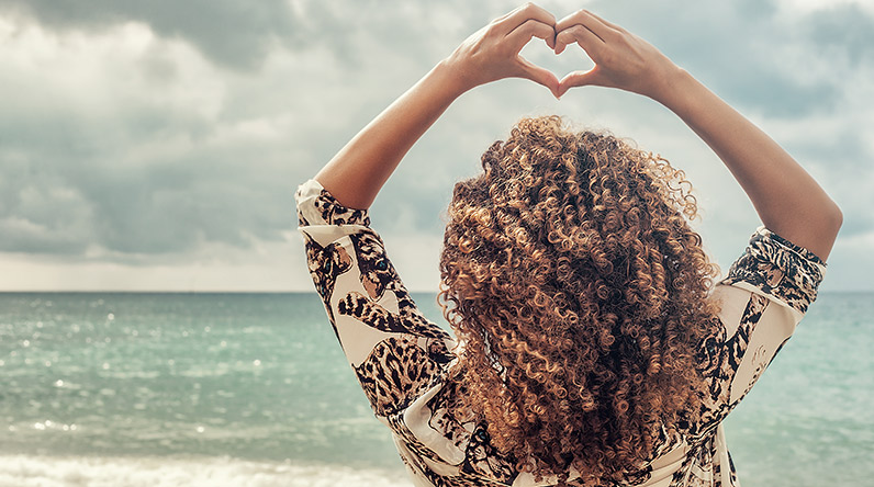 Woman with curly hair by the sea / Shutterstock