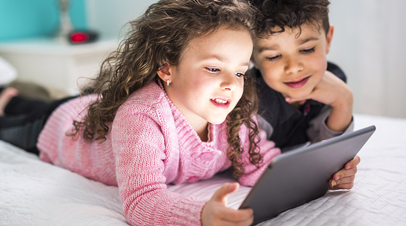 Brother and sister playing on a tablet / Shutterstock