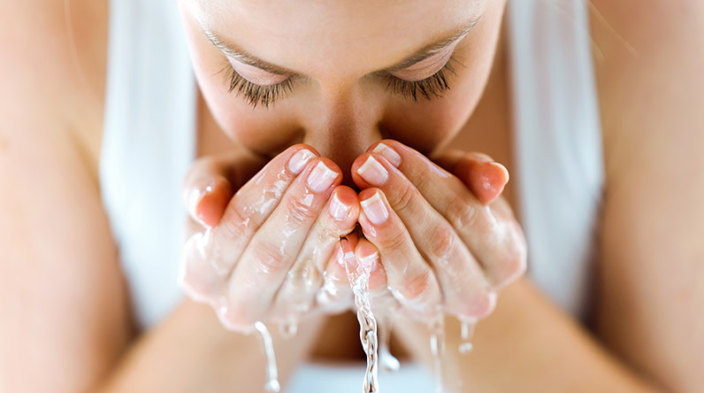 Woman washing her face with water / Shutterstock