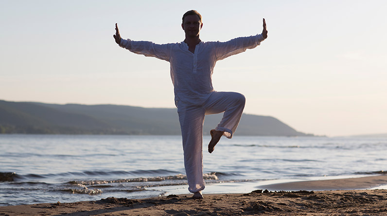 Man holding a Tai Chi pose on a beach / Shutterstock