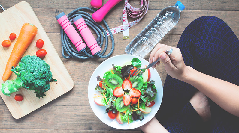 Woman eating healthy salad to lose weight / Shutterstock