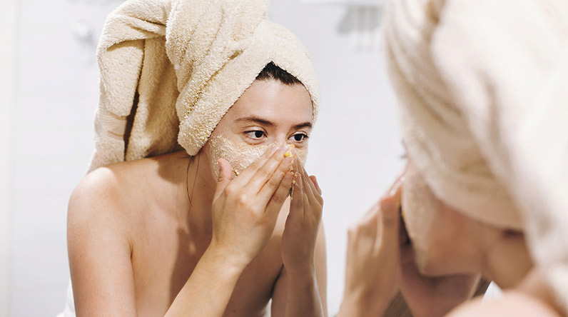 Woman exfoliating her face / Shutterstock