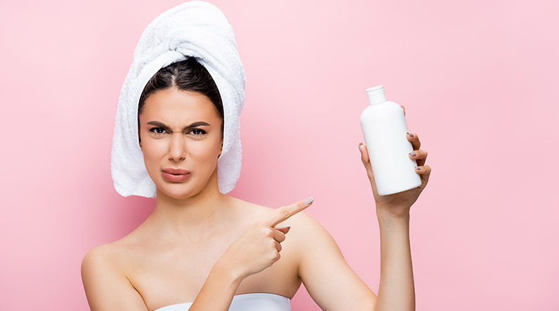 Woman with bottle of cream / Shutterstock