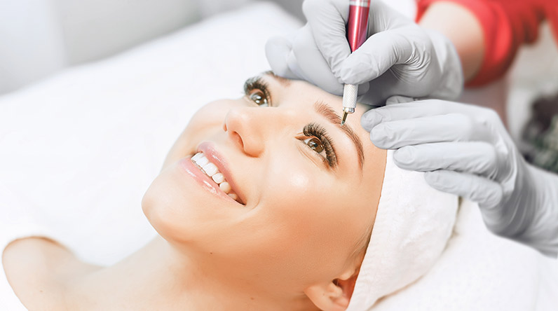 Smiling woman having microblading treatment / Shutterstock